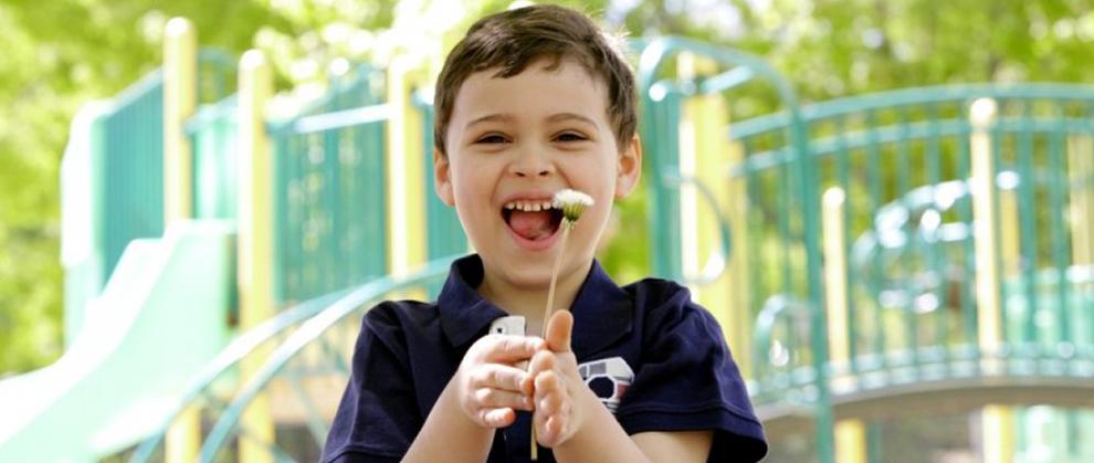 Menino sorridente segurando uma flor