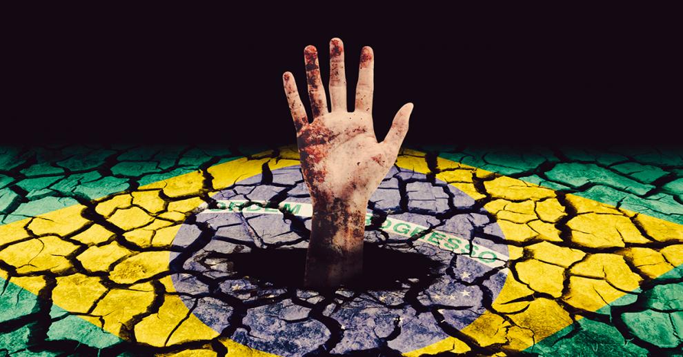 Uma mão sobre a bandeira do Brasil em um chão quebrado