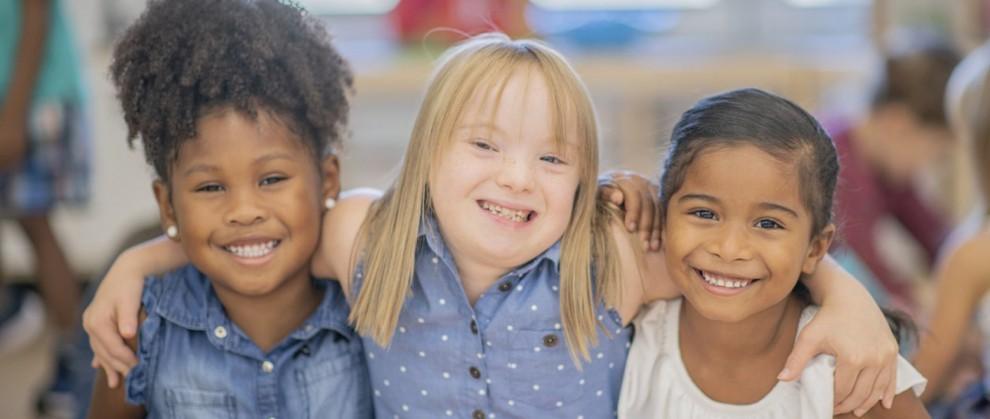 Três meninas se abraçando e sorrindo sendo que a do meio possui Síndrome de Down