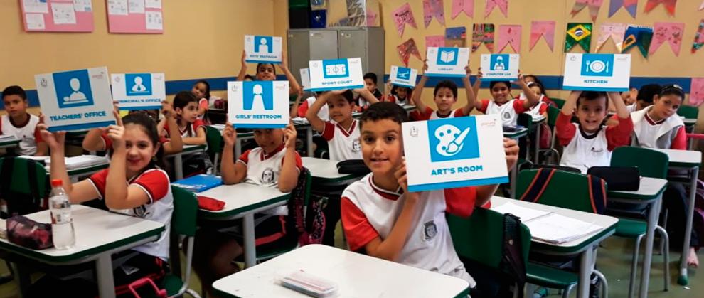 Crianças de Taboão da Serra segurando placas em inglês para a foto