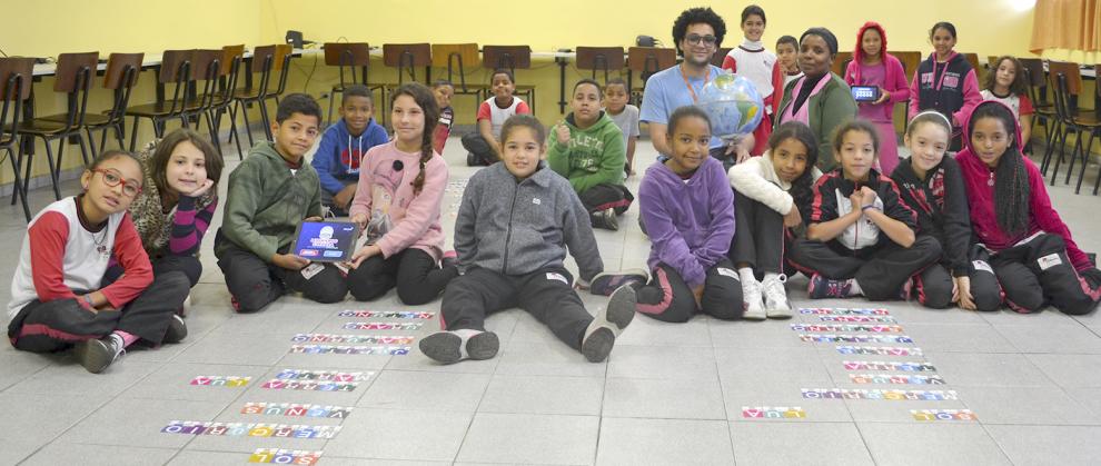 Crianças em sala de aula realizando uma atividade com uso de cartões de papel e tablet